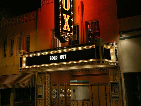 The outside of a theatre with lights around a black sign that says sold out. Text below says Drama for drama instruction.