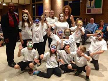 A group of enthusiastic children wearing white tshirts and masks. They are part of an acting or drama camp.