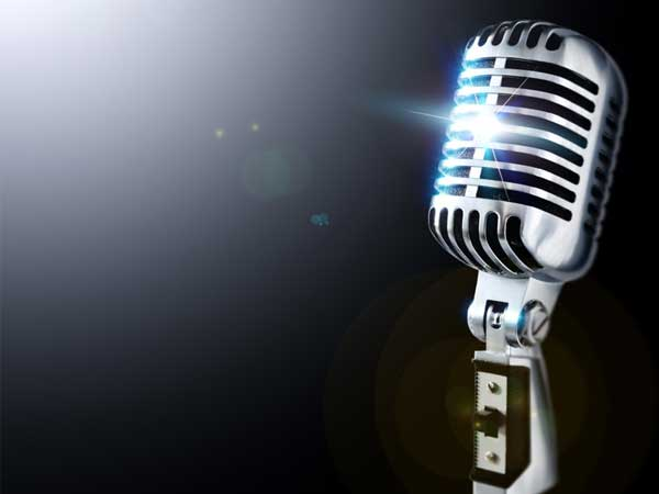 """An old fashioned looking microphone against a black background. Text below says """"vocal"""" for voice instruction."""